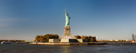 Foto de Panorama of island of Liberty with statue of Liberty seen from the ferry in the Hudson river. Symbol of the New york. - Imagen libre de derechos
