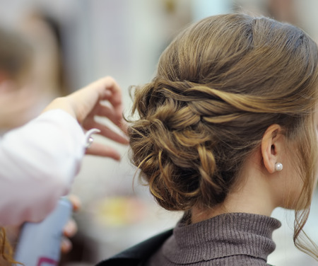 Foto de Young woman/bride getting her hair done before wedding or party. Wedding or prom ball hairstyles. - Imagen libre de derechos