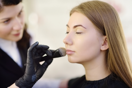 Foto de Beautician applying the tone of the foundation using special brush on face young beautiful model. Facial care and make up. Professional beauty salon - Imagen libre de derechos