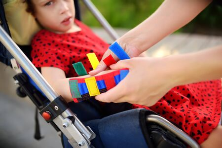 Foto de Mother puts orthosis on her daughter arms. Disabled girl sitting on a wheelchair. Child cerebral palsy. Inclusion. - Imagen libre de derechos