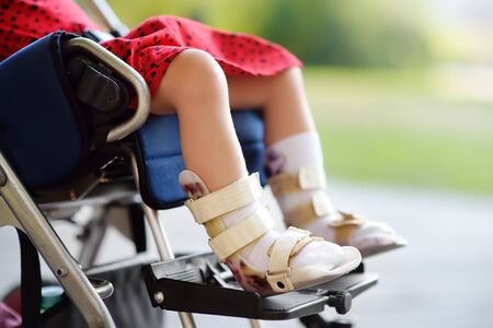 Foto de Disabled girl sitting in wheelchair. On her legs orthosis. Child cerebral palsy. Inclusion. Family with disabled kid. - Imagen libre de derechos