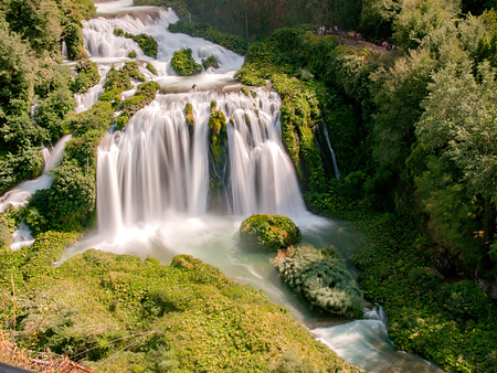 Foto de Marmore Falls, a waterfall nestled in a green forest on a beautiful summer day (Cascata delle Marmore, Umbria, Italy) - Imagen libre de derechos