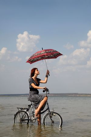 Girl go for a cycle ride at water with umbrella in hand.