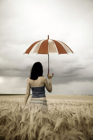Girl with umbrella at field in retro style