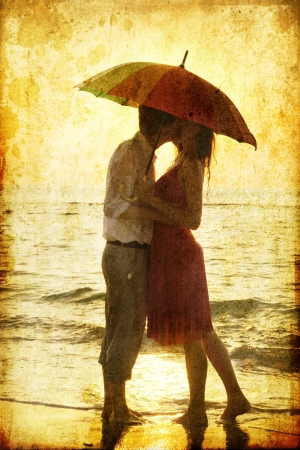 Photo for Couple kissing under umbrella at the beach in sunset. Photo in old image style. - Royalty Free Image