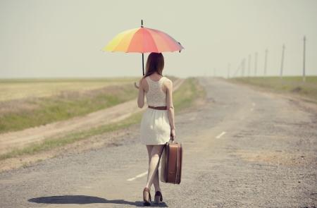 Redhead enchantress walking near rapeseed field. Photo in old image style.