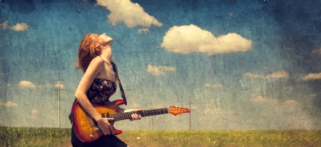 Photo pour Red-head girl with guitar. Photo in old image style. - image libre de droit