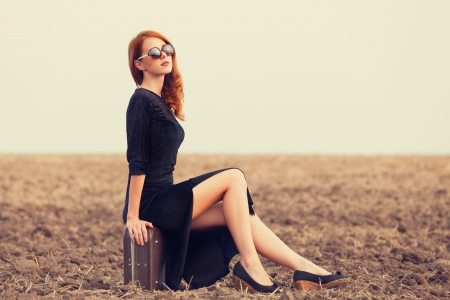 Foto de Fashion redhead women with suitcase at autumn field - Imagen libre de derechos