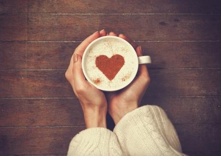 Foto de woman holding hot cup of coffee, with heart shape - Imagen libre de derechos