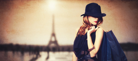 Photo pour Redhead women with shopping bags on parisian background. - image libre de droit