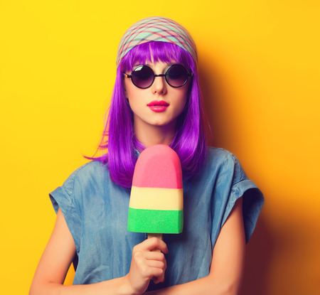 Photo pour Beautiful girl with violet hair in sunglasses and ice-cream on yellow background. - image libre de droit