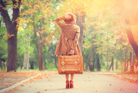 Foto de Redhead girl with suitcase in the autumn park. - Imagen libre de derechos