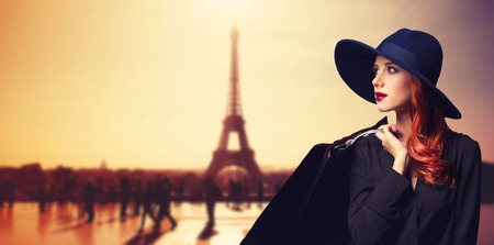 Photo pour Redhead women with shopping bags on parisian background. - image libre de droit