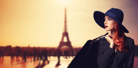 Foto de Redhead women with shopping bags on parisian background. - Imagen libre de derechos