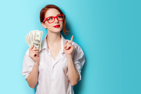 Portrait of redhead women in red glasses with money on blue background
