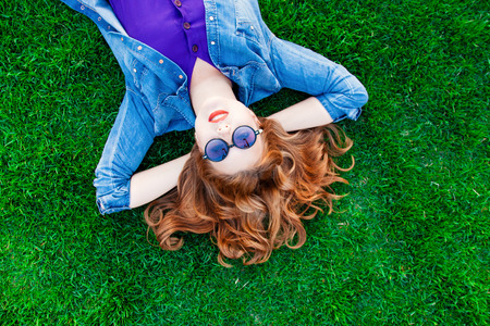 Foto de Beautiful redhead women lying down on green grass in summer time in the park. - Imagen libre de derechos