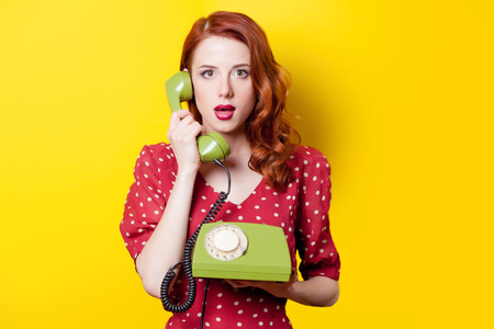 Foto de Surprised redhead girl in red polka dot dress with green dial phone on yellow background. - Imagen libre de derechos