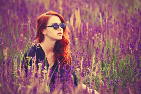 Photo for Portrait of a beautiful redhead girl with sunglasses on lavender field. - Royalty Free Image