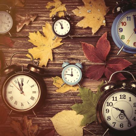 Photo pour Autumn leafs and alarm clock on wooden table. - image libre de droit