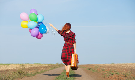 Photo pour Beautiful girl in plaid dress with multicolored balloons and bag on countryside - image libre de droit