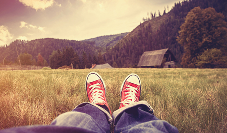Photo pour Young man in gumshoes and jeans have a rest on green grass in the mountains. - image libre de droit