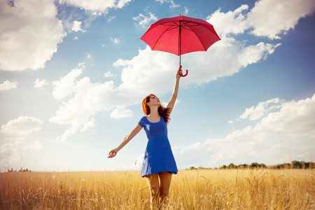 Foto de Beautiful redhead girl with umbrella at autumn countryside - Imagen libre de derechos