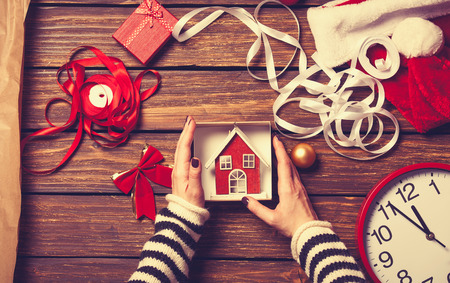 Photo pour Female hands are wrapping a christmas gift on wooden background - image libre de droit