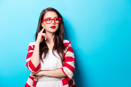 Photo pour beautiful young woman in glasses standing in front of wonderful blue background - image libre de droit