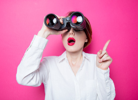Photo for Beautiful red-haired surprised businesswoman with binoculars on pink background - Royalty Free Image