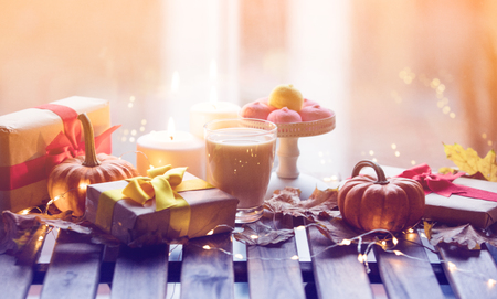 Photo for cup of coffee or tea near a pumpkin, gifts and candles with maple leaves and Fairy Lights  around on a wooden table near a window in rainy day. Autumn season image - Royalty Free Image