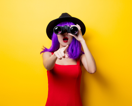 Photo for Portrait of young style hipster girl with purple hairstyle and binoculars on yellow background - Royalty Free Image