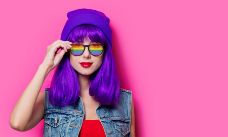 Photo pour Girl with purple hair and with rainbow eyeglasses on pink background - image libre de droit