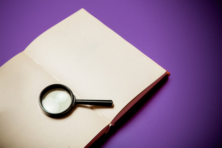 Photo for Magnifier and book on purple background - Royalty Free Image