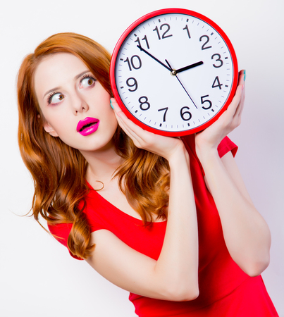 Foto de Surprised redhead girl in red dress with big clock on white background  - Imagen libre de derechos