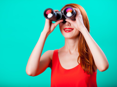 Photo for Young redhead girl with binoculars on mint background - Royalty Free Image