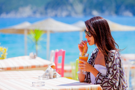 Photo pour Beautiful tourist woman drinking a juse in a restaurant on sea beach in Greece. - image libre de droit