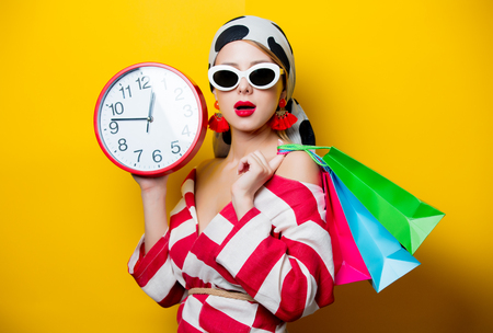 Photo for Portrait of beautiful style woman in sunglasses and striped clothes with alarm clock and shopping bags on yellow background - Royalty Free Image