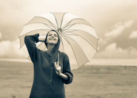 Photo pour Beautiful adult girl in sweater with umbrella at wheat field and cloudscape on background. Image in sepia color style - image libre de droit