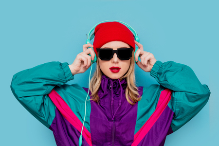 Photo pour Portrait of a woman in red hat, sunglasses and suit of 90s with headphones on blue background. - image libre de droit