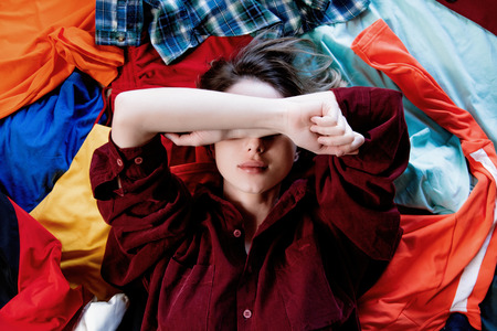 Photo for Upset woman keep hands over head and lying on clothes. Above view - Royalty Free Image