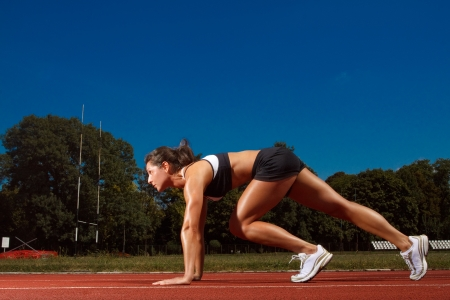 Athletic woman on track starting to run