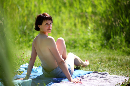Photo pour Beach season. Woman on the beach by the lake. Beautiful young woman bathes in the rays of the summer sun on the hill above the river. - image libre de droit