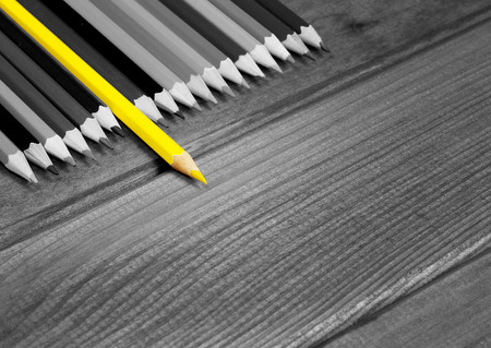 Photo pour Black and white image of colored pencils with isolated yellow pencil against a dark wooden table. The concept of leadership, business, Chief - image libre de droit
