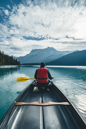 Photo for Young Man Canoeing on Emerald Lake in the rocky mountains canada with canoe and life vest with mountains in the background blue water. - Royalty Free Image