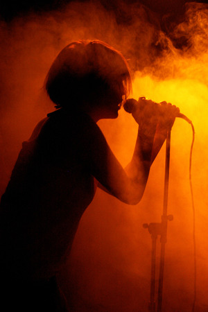 Photo for Concert photo of female singer silhouette holding microphone - Royalty Free Image