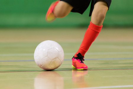 Foto de kid plays football soccer futsal  in the the sports hall - Imagen libre de derechos