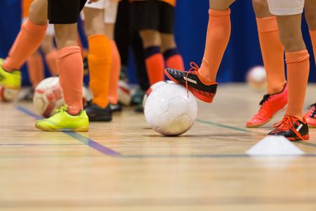 Foto per kids playing football soccer futsal  in the the sports hall - Immagine Royalty Free