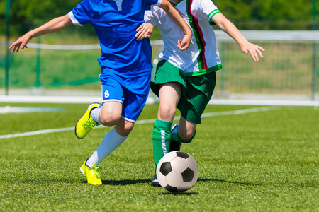 Photo pour young boys playing football soccer game. Running players in blue and white uniforms - image libre de droit