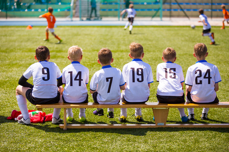 Photo pour Football soccer match for children. Kids waiting on a bench. - image libre de droit