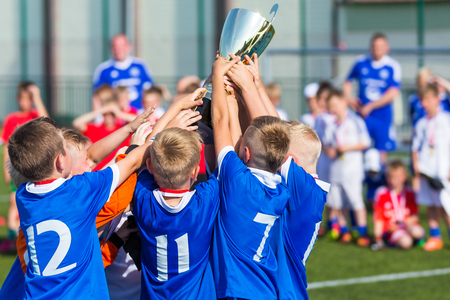 Photo pour Young Soccer Players Holding Trophy. Boys Celebrating Soccer Football Championship. Winning team of sport tournament for kids children. - image libre de droit